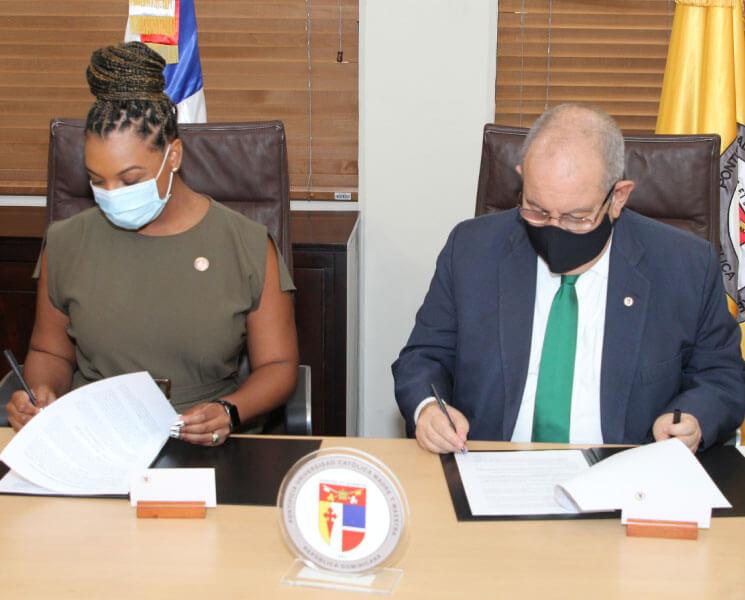 Firman el acuerdo, Doralyn De Dios, presidenta de la DBA y David Álvarez Martín, rector de la PUCMM